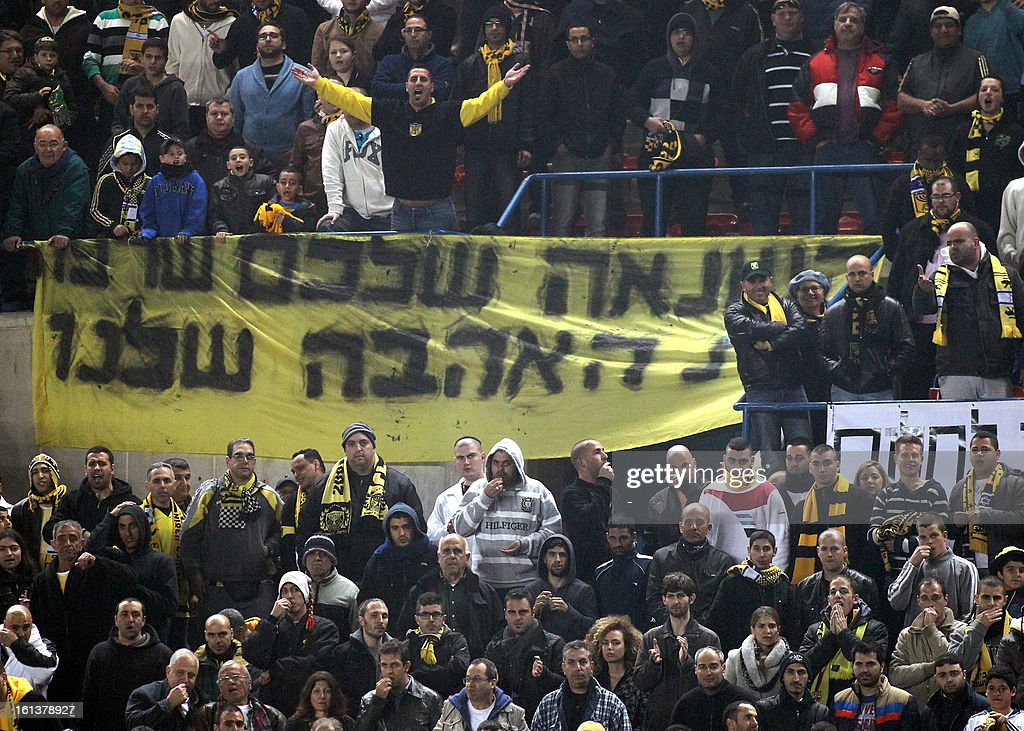 Beitar Jerusalem's supporters chant slogans beside a banner ''your hatred burned our love'' during an Israeli championship football match between Beitar Jerusalem and Bnei Sakhnin at the Teddy Kollek Stadium in Jerusalem on February 10, 2013. The Beitar Jerusalem soccer club hosted the Israeli Arab team Bnei Sakhnin in a highly charged atmosphere, only three days after indictments were filed against four Beitar fans over charges relating to racism. AFP PHOTO