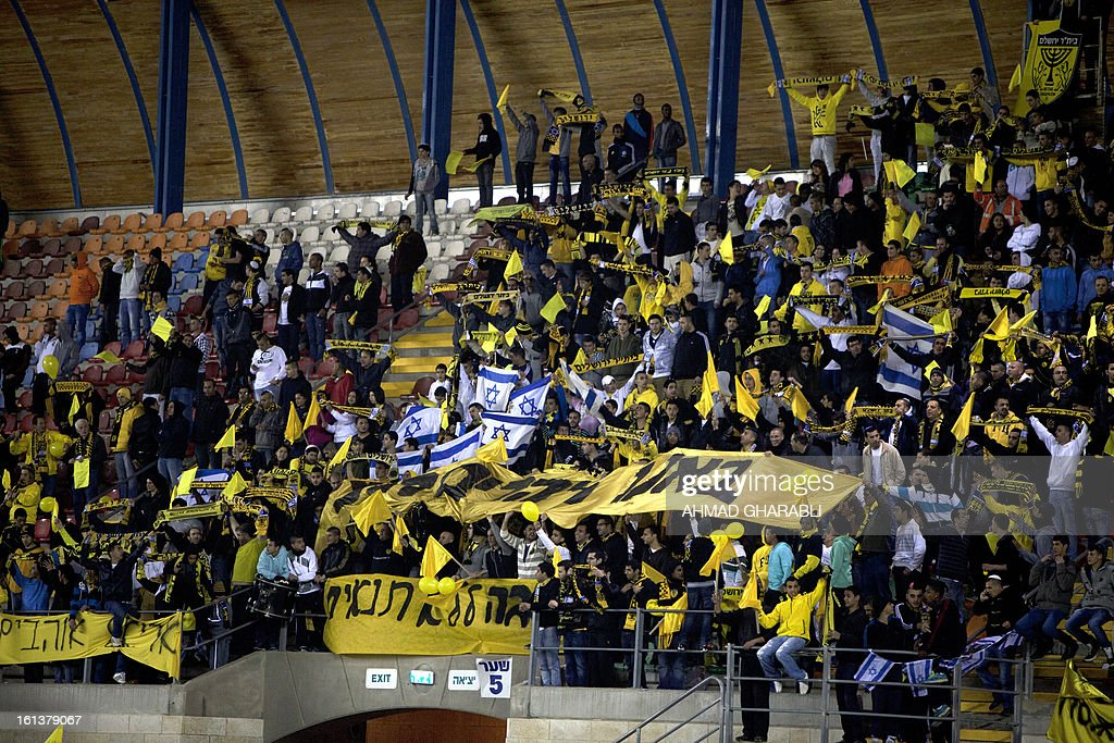 Beitar Jerusalem's supporters chant slogans during an Israeli championship football match between Beitar Jerusalem and Bnei Sakhnin at the Teddy Kollek Stadium in Jerusalem on February 10, 2013. The Beitar Jerusalem soccer club hosted the Israeli Arab team Bnei Sakhnin in a highly charged atmosphere, only three days after indictments were filed against four Beitar fans over charges relating to racism. AFP PHOTO / AHMAD GHARABLI