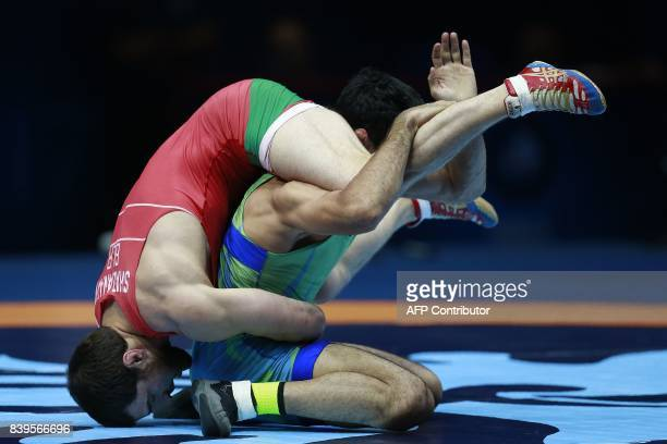 TOPSHOT Belarus' Ali Shabanau challenges Uzbekistan's Bekzod Abdurakhmonov during the men's freestyle wrestling 74kg category bronze medal playoffs...