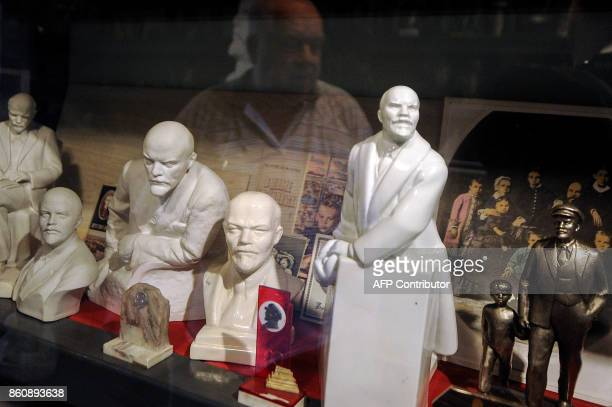 Belarus' collector Nikolai Pankrat is reflected in a glass case as he demonstrates the collection of busts and sculptures of Soviet State founder...
