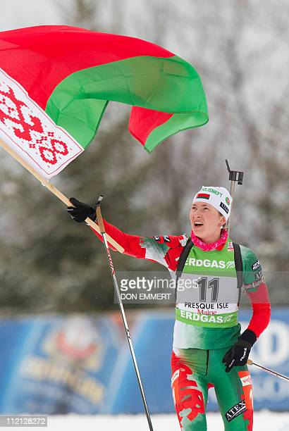 Belarus' Darya Domracheva carries a flag from a spectator to celebrate her third place finish in the IBU World Cup Biathlon Women's 10 km Pursuit on...