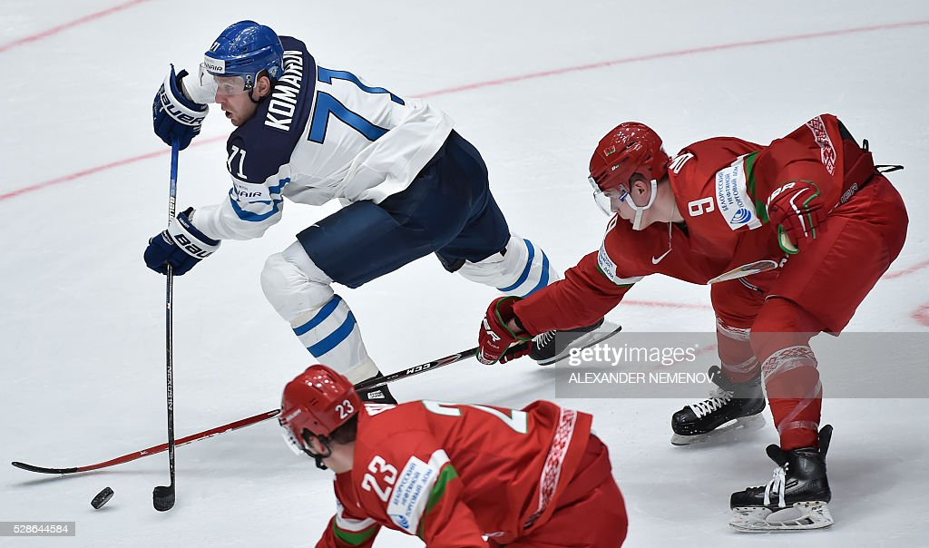 Belarus' defender Roman Dyukov (R) and Belarus' forward Andrei Stas (C) try to stop Finland's forward Leo Komarov during the group B preliminary round game Finland vs Belarus at the 2016 IIHF Ice Hockey World Championship in St. Petersburg on May 6, 2016. / AFP / ALEXANDER
