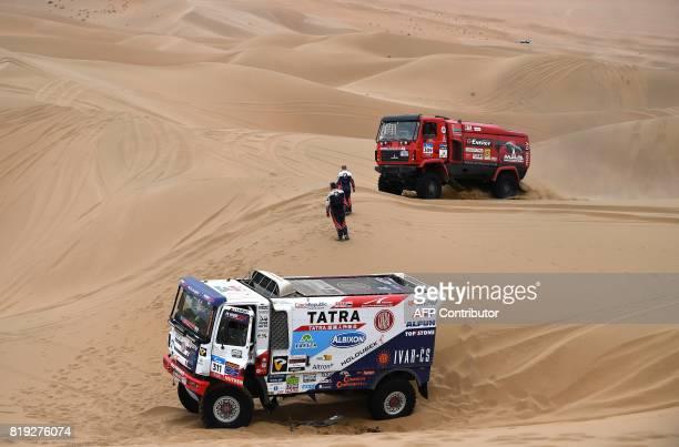 Belarus' driver Aleksandr Vasilevski codriver Dzmitry Vikhrenka and Anton Zaparoshchanka pass next to Tatra's Czech truck driver Martin Kolomy and...