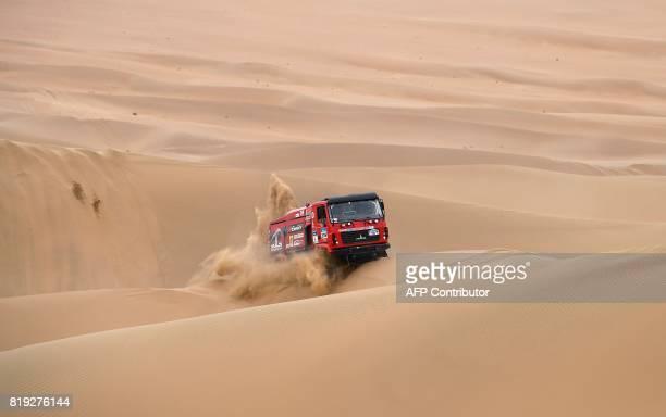 TOPSHOT Belarus' driver Aleksandr Vasilevski codriver Dzmitry Vikhrenka and Anton Zaparoshchanka ride over sand dunes while competing during the...