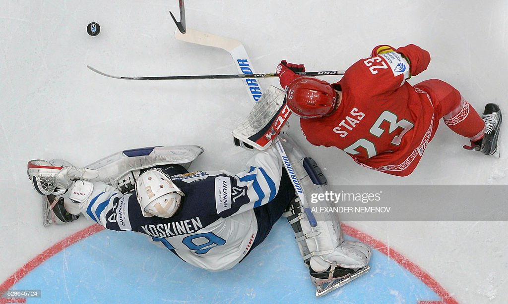 Belarus' forward Andrei Stas (R) attacks Finland's goalie Mikko Koskinen during the group B preliminary round game Finland vs Belarus at the 2016 IIHF Ice Hockey World Championship in St. Petersburg on May 6, 2016. / AFP / ALEXANDER