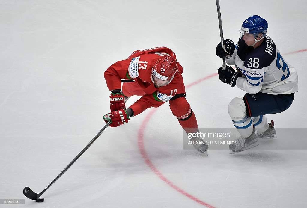 Belarus' forward Sergei Drozd (L) fights for the puck with Finland's defender Juuso Hietanen during the group B preliminary round game Finland vs Belarus at the 2016 IIHF Ice Hockey World Championship in St. Petersburg on May 6, 2016. / AFP / ALEXANDER