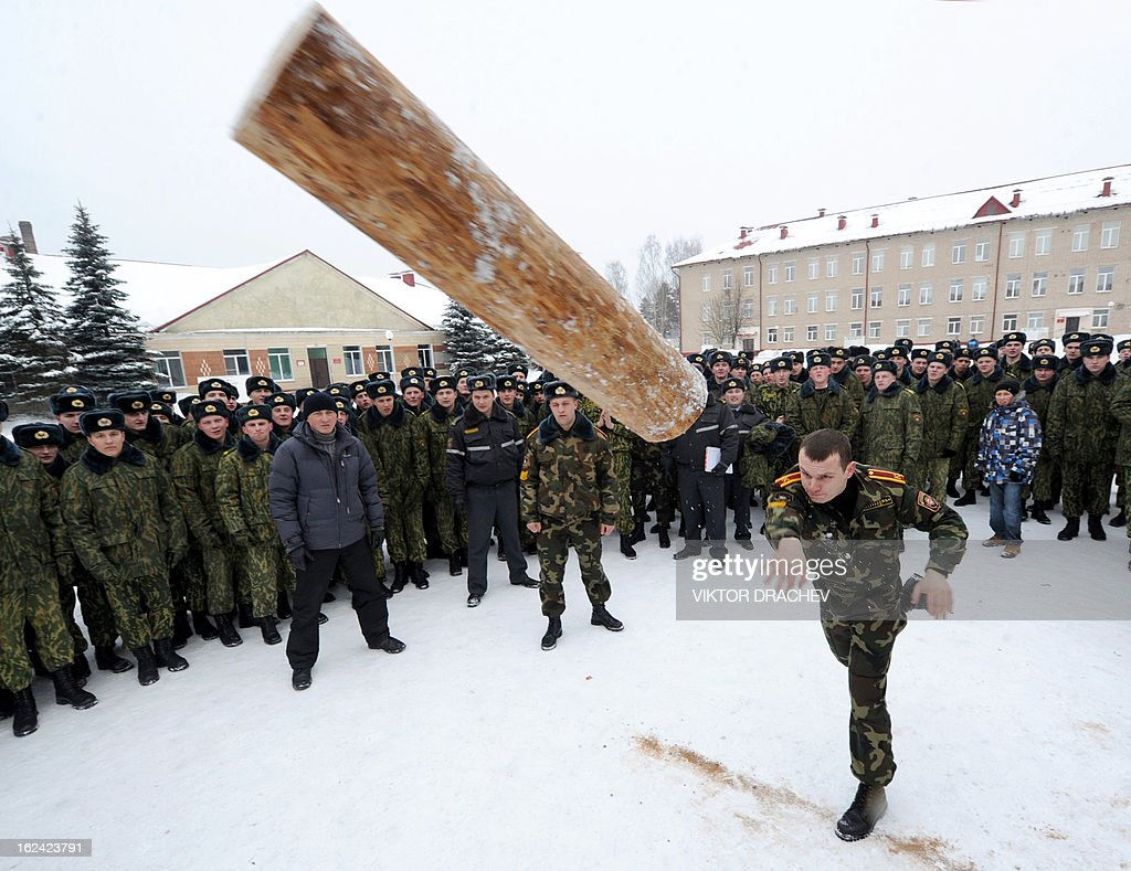Belarus Interior Ministry serviceman throws a beam as he takes part in a competition to mark the Defenders of Fatherland Day at their training center near the village of Okolitsa some 30 km outside Minsk, on February 23, 2013. Belarus alongside with some countries of former USSR markes the Defenders of Fatherland Day on February 23. AFP PHOTO/VIKTOR DRACHEV
