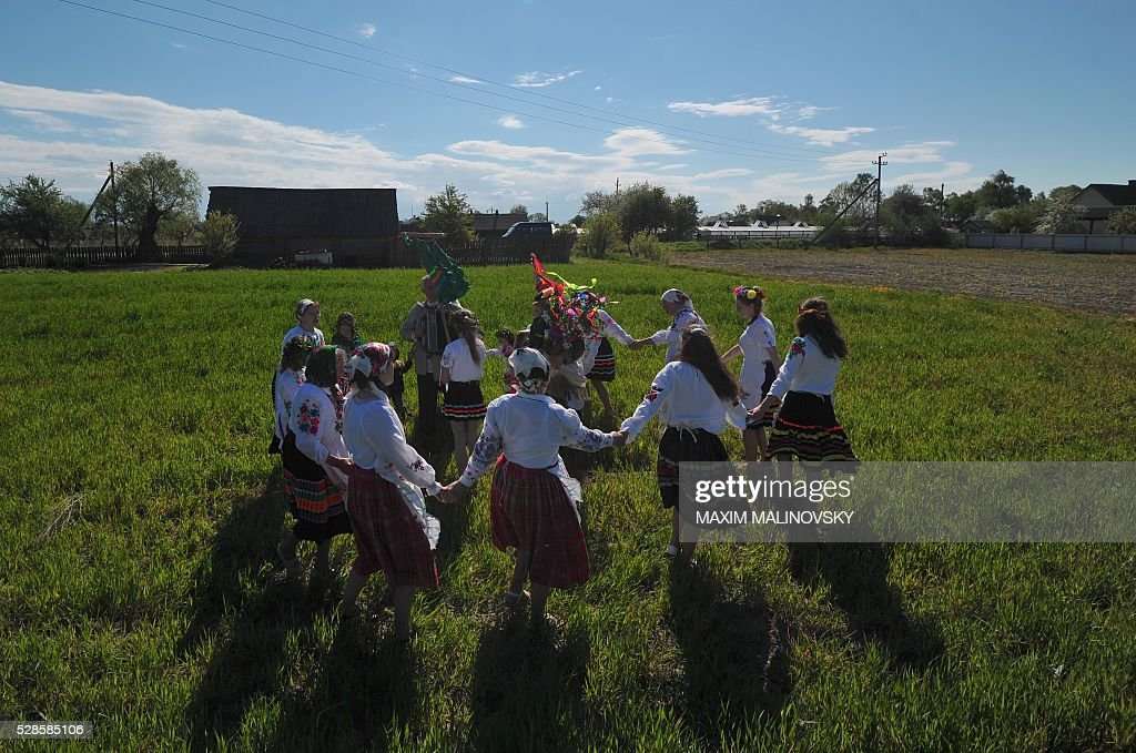 Belarus locals dance in a field during a traditional festival to pray for rich harvest in the village of Pogost, some 250 km south of Minsk, on May 6, 2016. / AFP / MAXIM