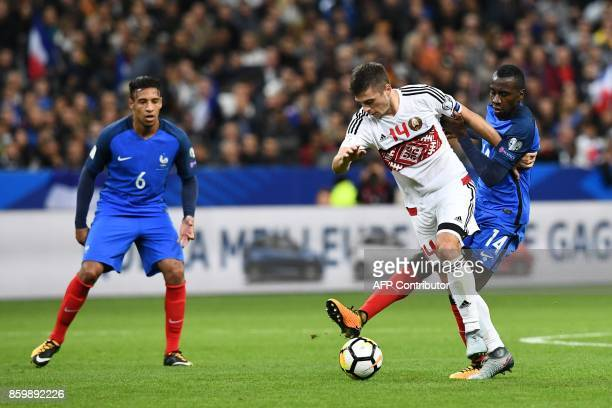 Belarus' midfielder Aleksandr Karnitski vies for the ball with France's midfielder Blaise Matuidi and France's midfielder Corentin Tolisso during the...