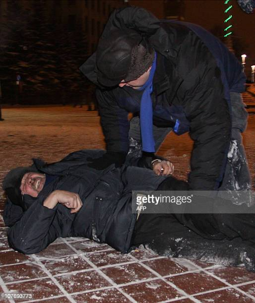 Belarus opposition candidate Andrei Sannikov lies on a street after being beaten during a clash between protesters and police in Minsk early on...