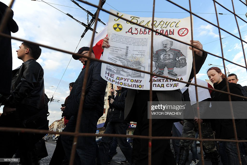 Belarus opposition supporters carry a poster with a caricature of President Alexander Lukashenko as they march in Minsk, on April 26, 2013, to commemorate the Chernobyl nuclear disaster victims on the 27th anniversary of the tragedy. The poster reads: 'Put the dictator on trial!'
