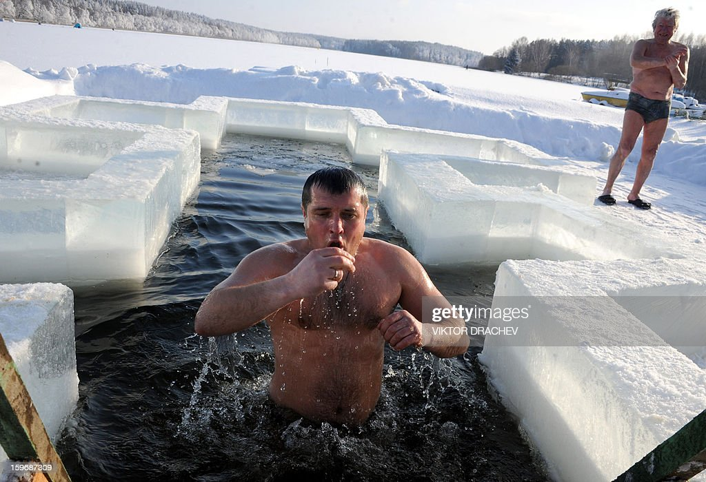 A Belarus Orthodox believer plunges into icy waters on the eve of the Epiphany holiday in Pilnitsa some 30 km outside Minsk, on January 18, 2013. Thousands of believers jumpe into holes cut in ice, braving freezing temperatures, on January 18 and early on January 19 to mark Epiphany, when they take part in a baptism ceremony. AFP PHOTO / VIKTOR DRACHEV
