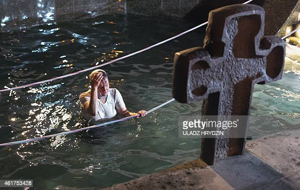 A Belarus Orthodox dips into the cold water on the eve of the Epiphany holiday in Minsk on January 18 2015 Thousands of believers jump into holes cut...