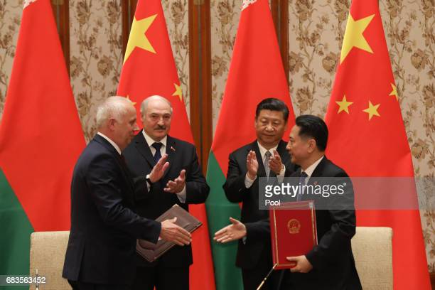 Belarus President Alexander Lukashenko and Chinese President Xi Jinping clap during a signing ceremony after a bilateral meeting at Diaoyutai State...