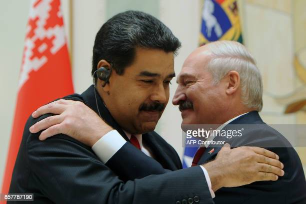 Belarus' President Alexander Lukashenko embraces his Venezuelan counterpart Nicolas Maduro during a joint press conference following their meeting in...
