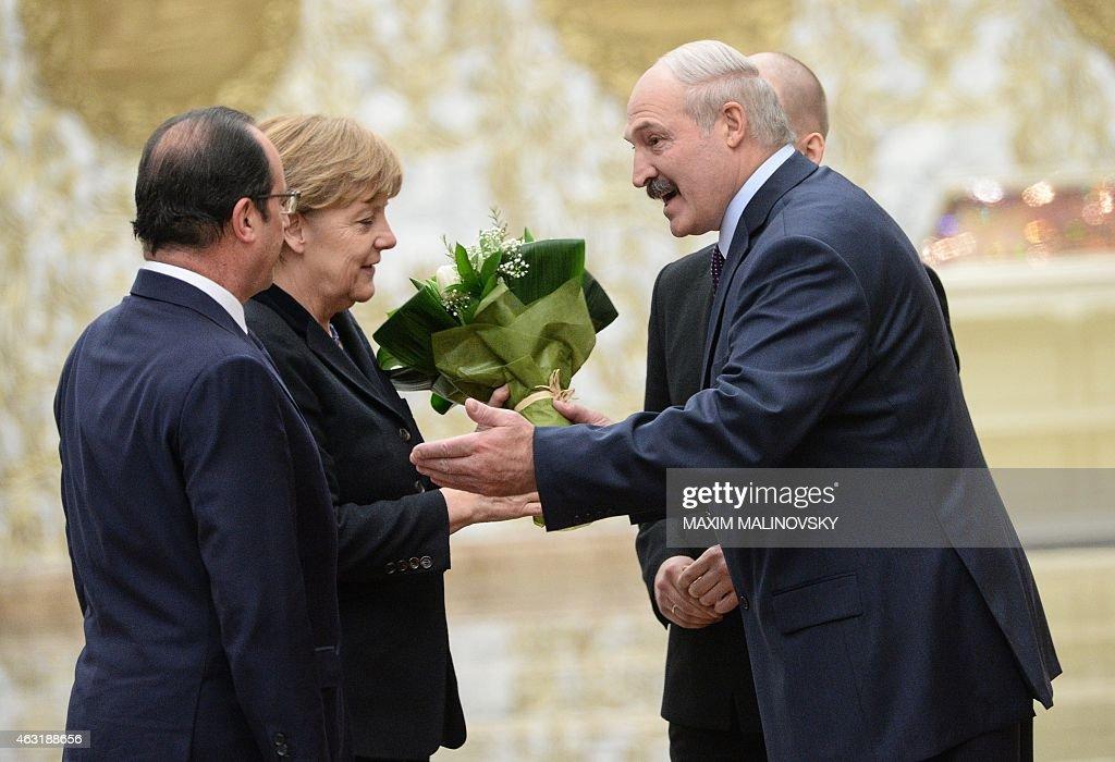 Belarus President Alexander Lukashenko gives flowers to German Chancellor Angela Merkel as he welcomes her and France's President Francois Hollande...