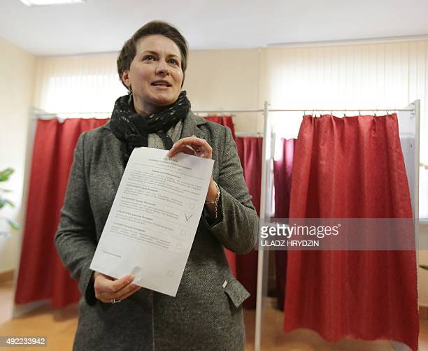 Belarus' Presidential candiadate Tatiana Karatkevich shows her ballot during presidential elections at a polling station in Minsk on October 11 2015...