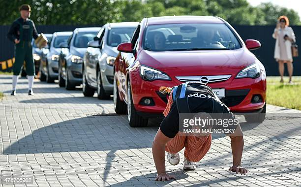 Belarus' strongman Kirill Shimko pulls a five car chain during the opening ceremony of a new General Motors' dealer center in Minsk on June 26 2015...