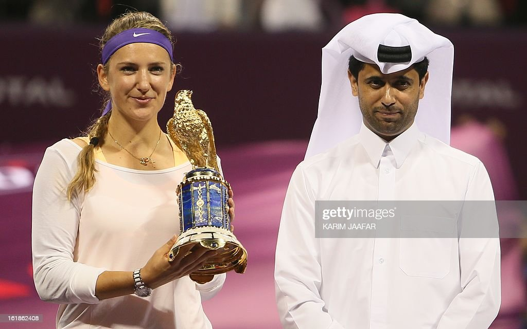 Belarus' Victoria Azarenka poses with the trophy along side Nasser al-Khelaifi, president of the Qatar Tennis Federation, after beating Serena Williams of the US in the Qatar WTA Open final tennis match in Doha on February 17, 2013. Azarenka won the match 7-6 (8/6), 2-6, 6-3 to retain her Qatar Open title, only her second win in 13 meetings with the American.