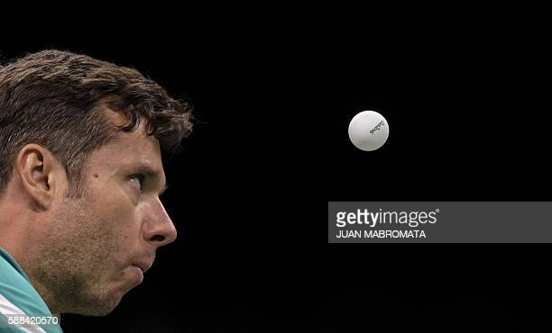 Belarus' Vladimir Samsonov eyes the ball as he serves against China's Zhang Jike in their men's singles semifinal table tennis match at the Riocentro...