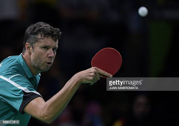 Belarus' Vladimir Samsonov hits a shot against China's Zhang Jike in their men's singles semifinal table tennis match at the Riocentro venue during...