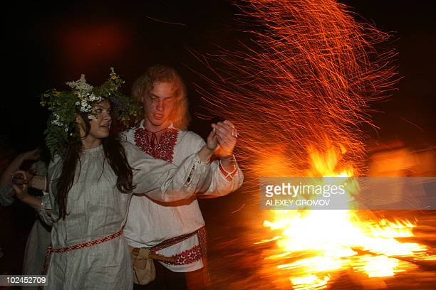 A Belarusian couple wearing traditional clothing dance near a campfire while celebrating Ivan Kupala Night a traditional Slavic holiday 25km from...