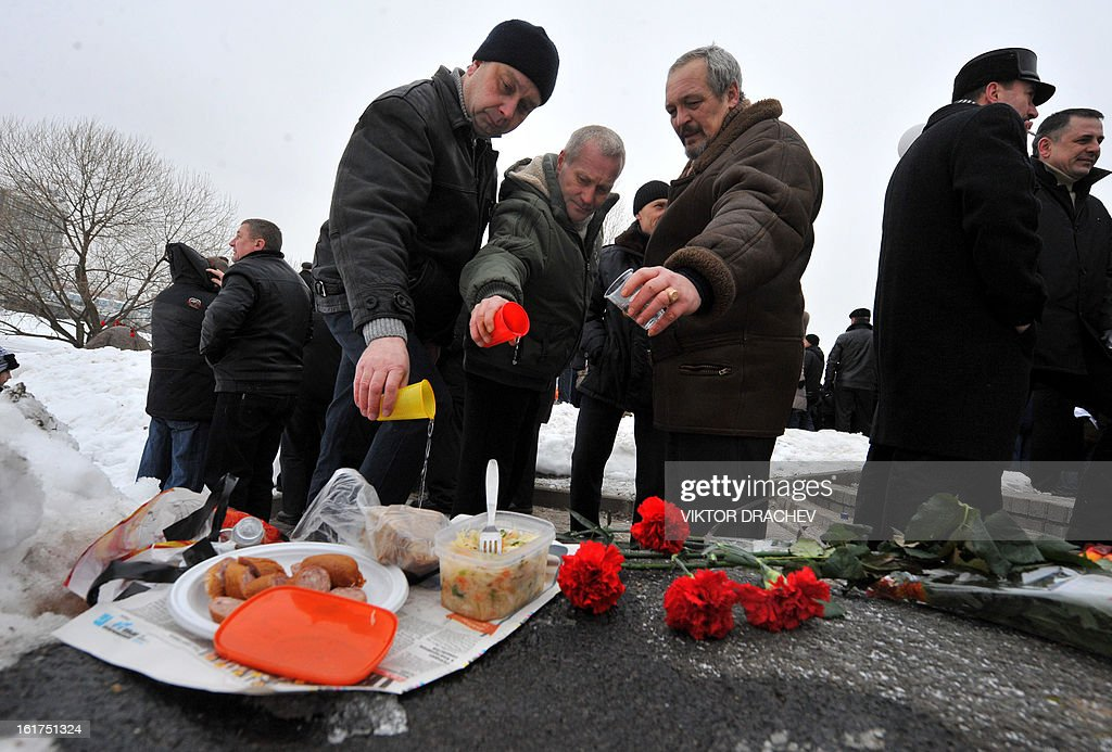 Belarusian men pour vodka at a monument to those Soviet soldiers born in Belarus, who was killed in Afghanistan while fighting against the Afghan rebels in the 1980s, in Minsk, on February 15, 2013. The ex-Soviet nation of Belarus marked today the 24th anniversary of the Soviet troops withdrawal from Afghanistan.
