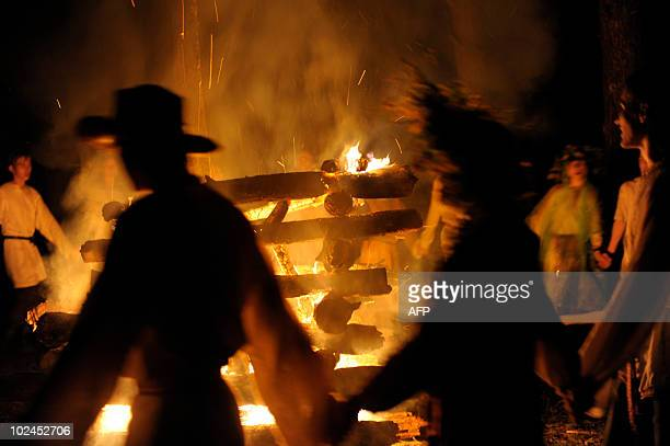Belarussians in traditional clothing dance around a fire while celebrating Ivan Kupala Night a traditional Slavic holiday marking midsummer outside...