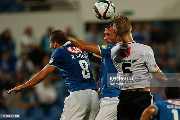 Belenenses's defender Tonel heads for the ball with Belenenses's midfielder Andre Sousa and Altach's midfielder Philipp Netzer during the UEFA Europa...