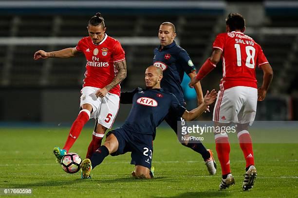 Belenenses's midfielder Hassan Yebda vies for the ball with Benfica's midfielder Ljubomir Fejsa Benfica's forward Eduardo Salvio and Belenenses's...