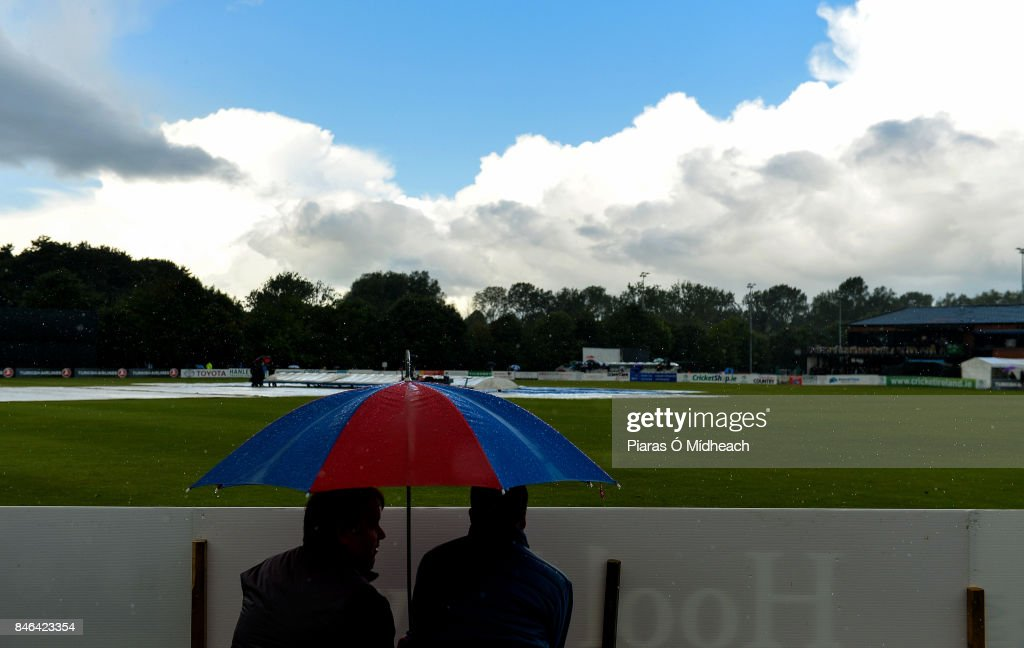 Belfast , Ireland - 13 September 2017; Spectators shelter from the rain under an umbrella as they await the result of a pitch inspectation before the One Day International match between Ireland and West Indies at Stormont in Belfast.