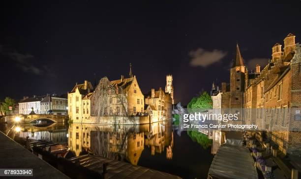 Belfry of Bruges and romantic Rozenhoedkaai canal illuminated at night with clear sky and stars in Flanders, Belgium