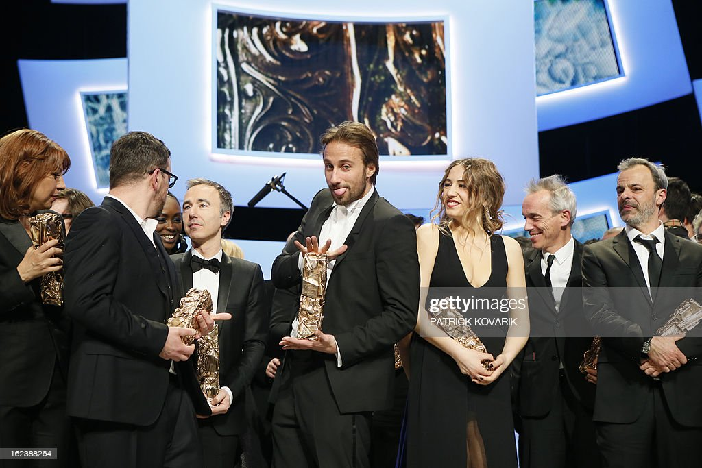 Belgian actor Matthias Schoenaerts (C) reacts beside and French singer and actress Izia Higelin (C, R) as they pose with their trophies at the end of the 38th Cesar Awards ceremony on February 22, 2013 at the Chatelet theatre in Paris. AFP PHOTO / PATRICK KOVARIK