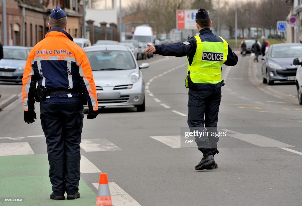 A Belgian (L) and a French police officers take part in a road traffic control on March 18, 2013 near the border in Tourcoing, northern France, as part of a Franco-Belgian cooperation agreement between police and customs. AFP PHOTO PHILIPPE HUGUEN