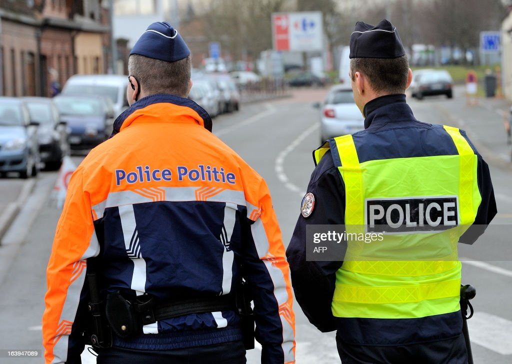 A Belgian (C) and a French police officers take part in a road traffic control on March 18, 2013 near the border in Tourcoing, northern France, as part of a Franco-Belgian cooperation agreement between police and customs.