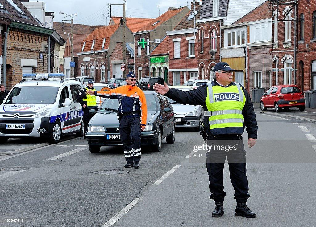 A Belgian (L) and a French police officers take part in a road traffic control on March 18, 2013 near the border in Tourcoing, northern France, as part of a Franco-Belgian cooperation agreement between police and customs.
