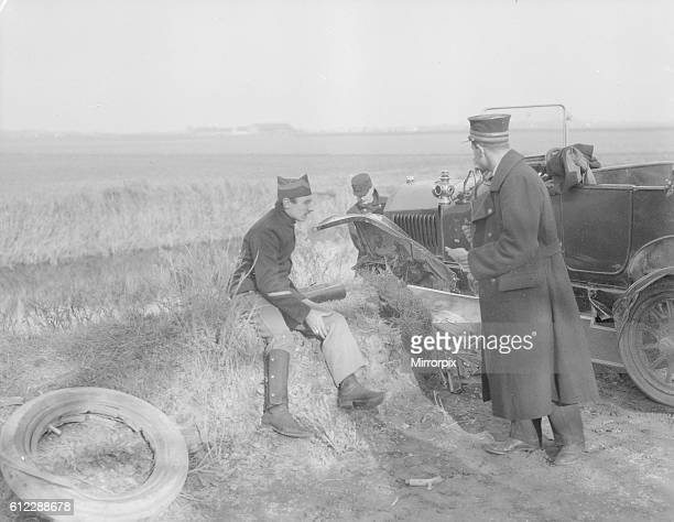Belgian and French officers inspect a car which crashed and nearly tumbled down the embankment into ditch on the Veurne road Circa November 1914
