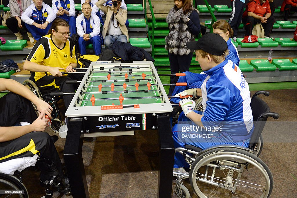 Belgian (L) and Russian (R) disabled competitors take part in the ITSF 2013 table soccer (aka babyfoot) World Cup on January 4, 2013 in Nantes, western France.