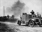 A Belgian armored car sending a rain of shot into the German ranks on the outskirts of Antwerp while the officer is watching the bombardment of...