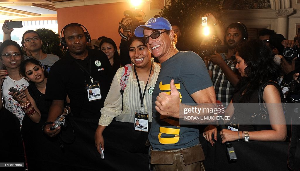 Belgian born Hollywood action star actor Jean-Claude Van Damme (centre R) poses with a fan as he arrives for the 14th International Indian Film Academy (IIFA) at The Venetian hotel in Macau on July 5, 2013. The annual IIFA Awards, India's Hindi language film industry, Bollywood's glitziest awards ceremony, which have been held overseas for the last 13 years, is one of the world's most-watched annual entertainment ceremonies, broadcast to nearly 500 million viewers in 110 countries. AFP PHOTO/Indranil MUKHERJEE