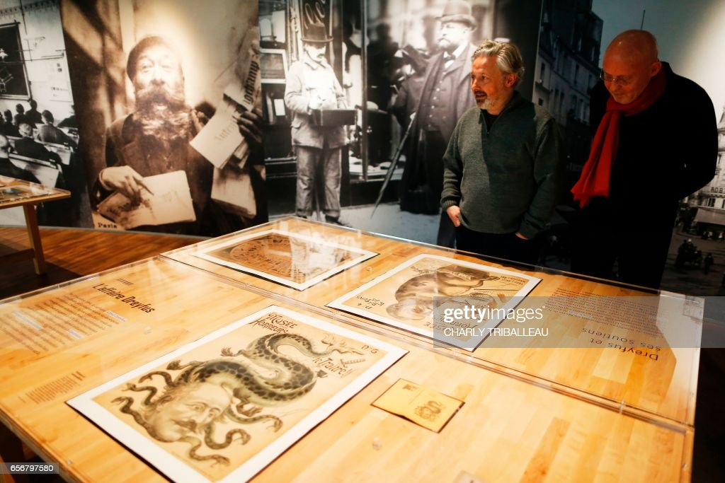 CORRECTION - Belgian collector Arthur Langerman (R) and director of the Memorial of Caen Stephane Grimaldi look at documents in the Memorial of Caen on March 21, 2017 in Caen, northwestern France. With over 120 pre-war caricatures, the exhibition at the Memorial of Caen show how the anti-Semite propaganda has shaped the spirits and nazism. The drawings are owned by Arthur Langerman whose almost entire family was killed during the Holocaust. / AFP PHOTO / CHARLY TRIBALLEAU / RESTRICTED TO EDITORIAL USE - TO ILLUSTRATE THE EVENT AS SPECIFIED IN THE CAPTION / The erroneous mention appearing in the metadata of this photo by CHARLY TRIBALLEAU has been modified in AFP systems in the following manner: COLLECTOR instead of HOARDER. Please immediately remove the erroneous mention from all your online services and delete it from your servers. If you have been authorized by AFP to distribute it to third parties, please ensure that the same actions are carried out by them. Failure to promptly comply with these instructions will entail liability on your part for any continued or post notification usage. Therefore we thank you very much for all your attention and prompt action. We are sorry for the inconvenience this notification may cause and remain at your disposal for any further information you may require.