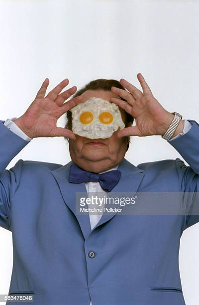 Belgian comedian Raymond Devos holds fried eggs over his eyes