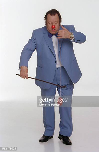Belgian comedian Raymond Devos wears a clown nose while playing with a yoyo
