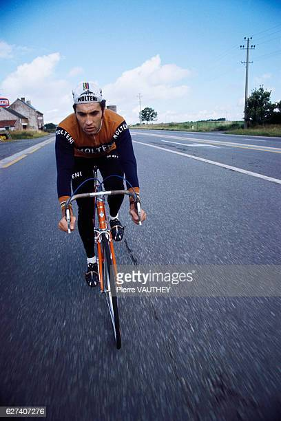 Belgian cycling champion Eddy Merckx bicycling down a street in the 1974 French film La Course en Tete The film was directed by Joel Santoni