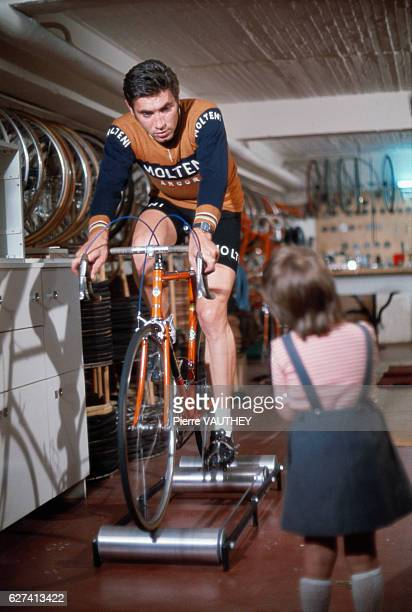 Belgian cycling champion Eddy Merckx talks to his daughter Sabrina as he tries out a bicycle in the 1974 French film La Course en Tete The film was...