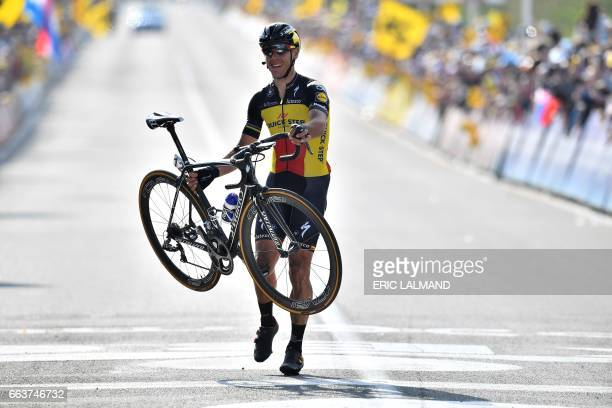 TOPSHOT Belgian cyclist Philippe Gilbert of QuickStep Floors gets off his bike to cross the finish line and win the 101st edition of the Ronde van...