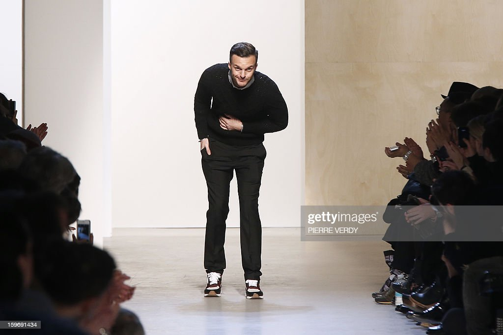 Belgian designer Kris Van Assche acknowledges the audience at the end of his Fall-Winter 2013-2014 collection show on January 18, 2013 during the men's fashion week in Paris. AFP PHOTO / PIERRE VERDY