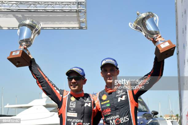 Belgian driver Thierry Neuville and compatriot codriver Nicolas Gilsoul of Hyundai i20 Coupe WRC hold their trophies as they celebrate their third...