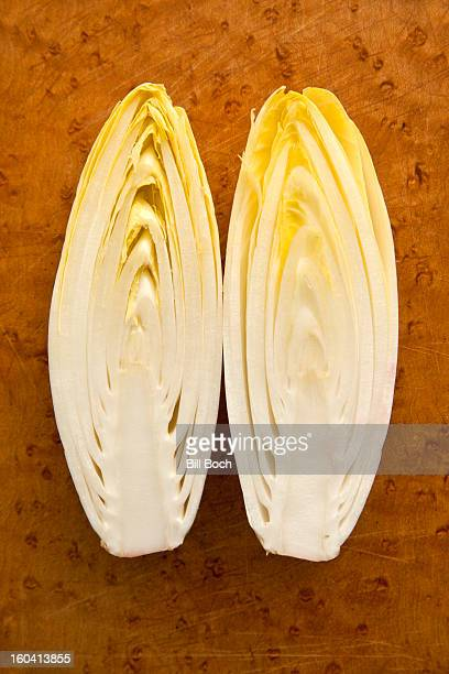 Belgian endive halved on a cutting board