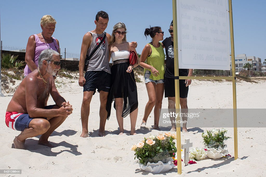 Belgian, English and Tunisian tourists take a moment to remember the victims of the 2015 Sousse Beach terrorist attack at a memorial sign on the beach in front of the Imperial Marhaba hotel on June 26, 2016 in Sousse, Tunisia. Today marks the one year anniversary of the Sousse Beach terrorist attack, which killed 38 people including 30 Britons. Before the 2011 revolution, tourism in Tunisia accounted for approximately 7% of the country's GDP. The two 2015 terrorist attacks at the Bardo Museum and Sousse Beach saw tourism numbers plummet even further forcing hotels to close and many tourism and hospitality workers to lose their jobs.